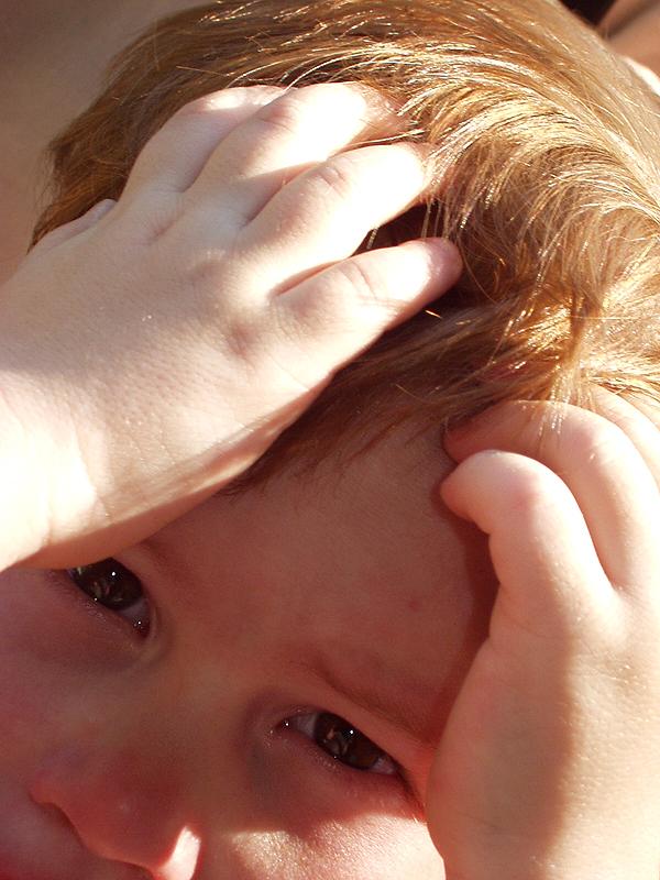 Niño tocándose el pelo como quitar liendres